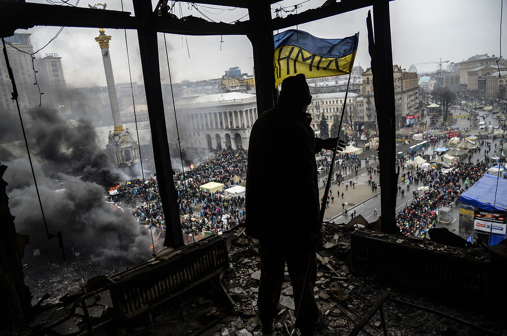 . A protester holds an Ukrainian national flag from a burned building during a face-off against police on February 20, 2014 in Kiev. AFP PHOTO/BULENT  KILIC/AFP/Getty Images