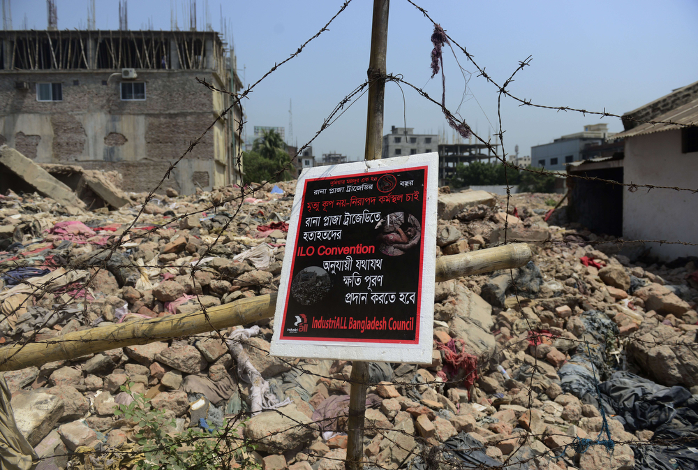 """. A poster tied to a fence at the scene of the Bangladesh Rana Plaza building collapse and reading, \""""We want a safe work place, not a death trap\' is seen on the first anniversary of the disaster on the outskirts of Dhaka on April 24, 2014. The Rana Plaza building collapsed on April 24, 2013, killing 1138 workers in the world\'s worst garment factory disaster. Western fashion brands faced pressure to increase help for victims as mass protests marked the anniversary. Thousands of people, some wearing funeral shrouds, staged demonstrations at the site of the now-infamous Rana Plaza factory complex.  (MUNIR UZ ZAMAN/AFP/Getty Images)"""