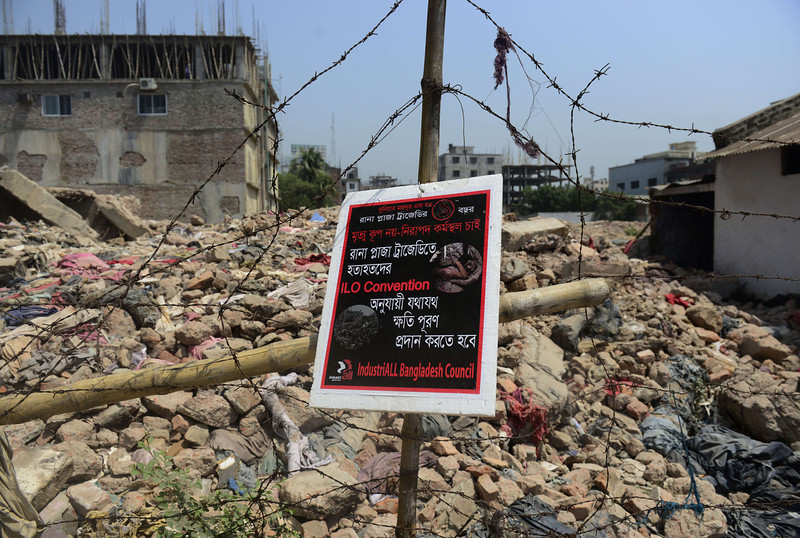 ". A poster tied to a fence at the scene of the Bangladesh Rana Plaza building collapse and reading, ""We want a safe work place, not a death trap\' is seen on the first anniversary of the disaster on the outskirts of Dhaka on April 24, 2014. The Rana Plaza building collapsed on April 24, 2013, killing 1138 workers in the world\'s worst garment factory disaster. Western fashion brands faced pressure to increase help for victims as mass protests marked the anniversary. Thousands of people, some wearing funeral shrouds, staged demonstrations at the site of the now-infamous Rana Plaza factory complex.  (MUNIR UZ ZAMAN/AFP/Getty Images)"