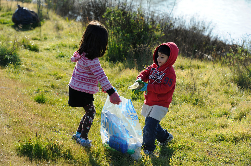. (names cq) Kaia Marbin, 4, holds her bag of recyclables open as her brother Jahan Marbin, 3, adds a bottle at an event where volunteers of all ages came together to honor Martin Luther King Jr. for a day of service at  Martin Luther King Jr. Shoreline Park  in Oakland, Calif., on Monday, Jan. 21, 2013. (Susan Tripp Pollard/Staff)