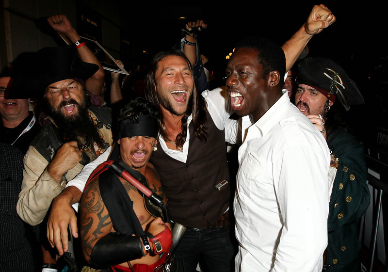 """. Zach McGowan, left, and Hakeem Kae-Kazim pose with fans before the fan sneak peek screening of \""""Black Sails\"""" during San Diego Comic-Con on Thursday, July 18, 2013 in San Diego, Calif. \""""Black Sails\"""" premieres on STARZ January 2014. (Photo by Matt Sayles/Invision for STARZ/AP Images)"""