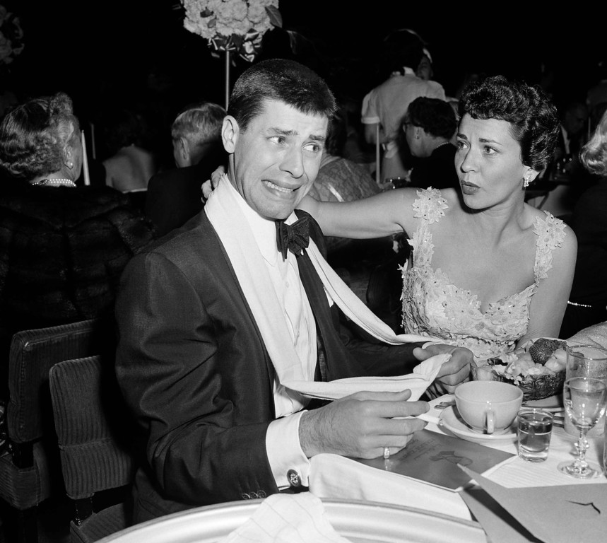 . Comedian Jerry Lewis looks unhappy about arriving late for Adolph Zukor\'s birthday party January 7, 1953 in Hollywood, Calif.       Lewis\' wife Patti tries to reasure him.   (AP Photo/ Harold Filan)