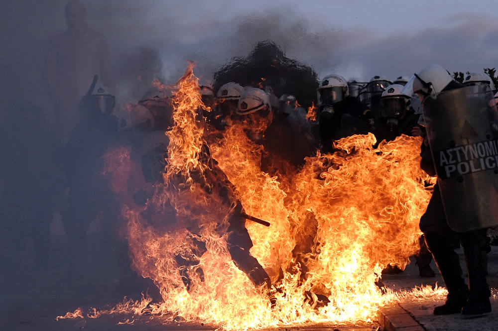 Description of . A riot police is engulfed by flames during clashes with protestors  in Athens on February 12, 2012. Greek police today used tear gas on petrol bomb-throwing protesters outside parliament where lawmakers were debating a new austerity plan aimed at staving off bankruptcy. AFP PHOTO / ARIS  MESSINIS/AFP/Getty Images