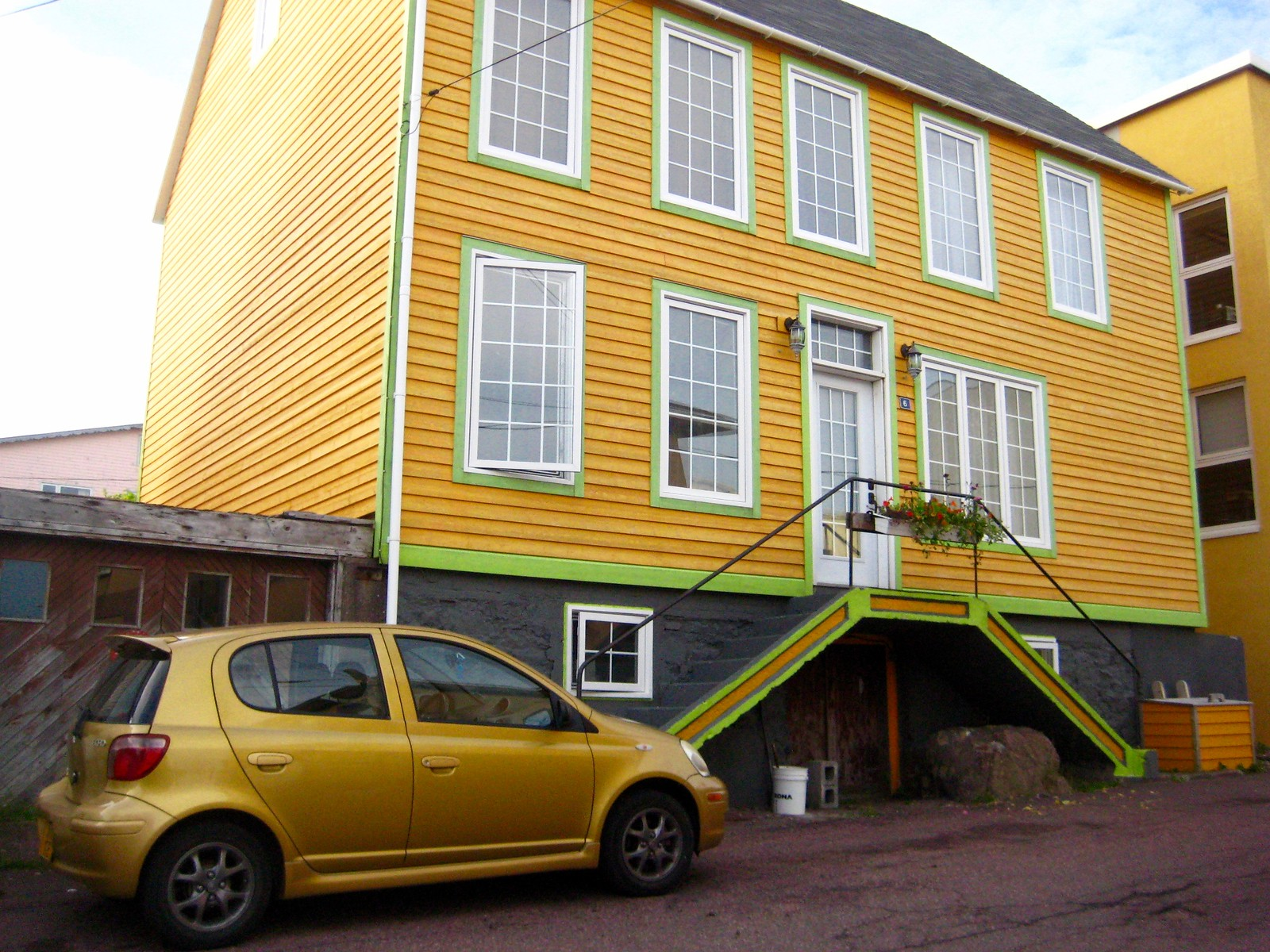 yellow clapboard house in St. Pierre with a yellow car parked in front
