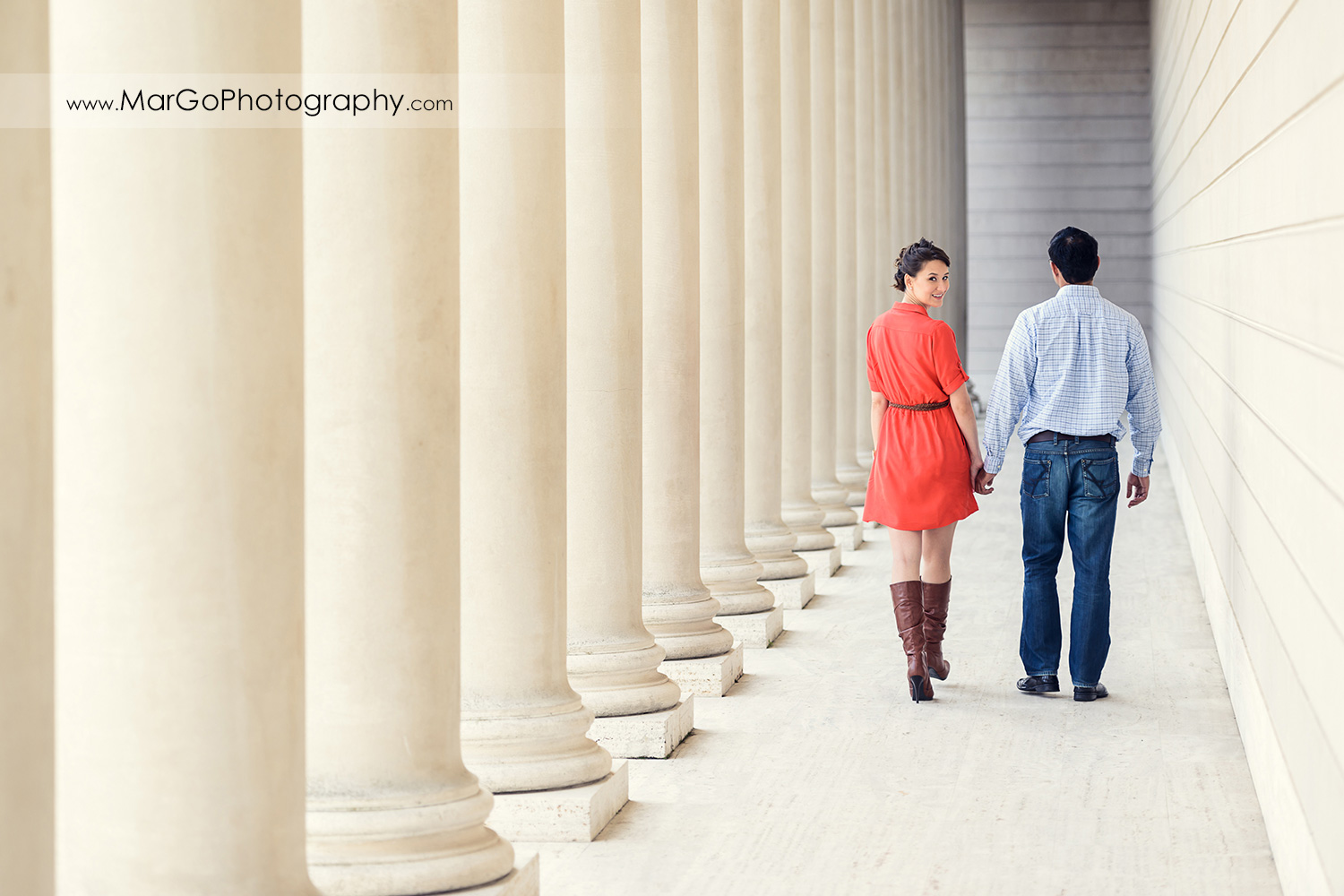 man in blue shirt and woman in red dress walking between white columns and wall during engagement session at San Francisco Legion of Honor