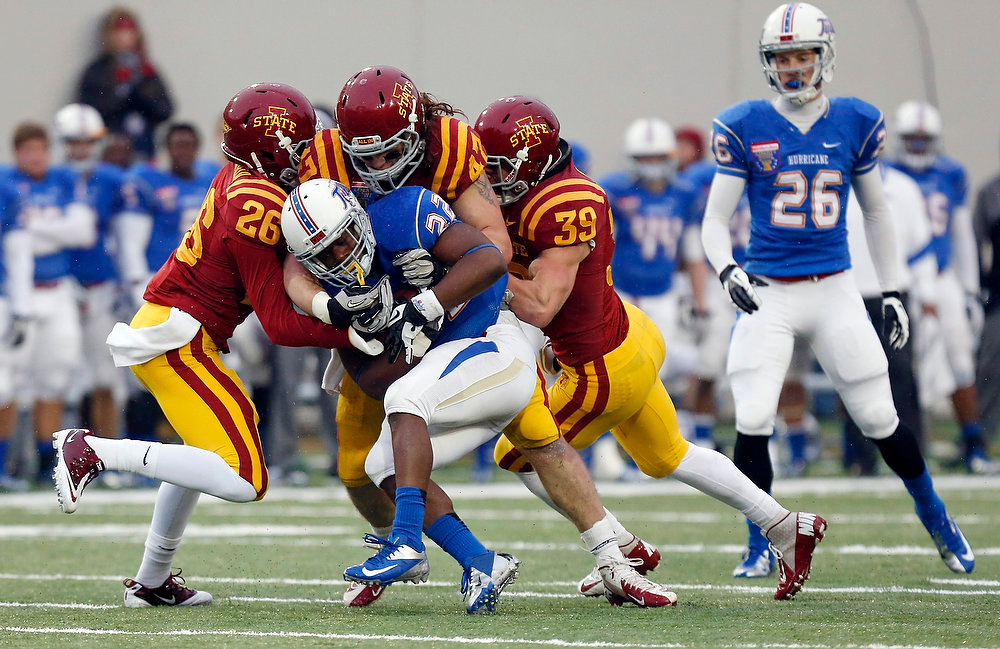 . Iowa State defensive backs Deon Broomfield (26) and Marcus Pate (39), and linebacker A.J. Klein (47) tackle Tulsa running back Trey Watts (22) after a short gain in the first half of the Liberty Bowl NCAA college football game in Memphis, Tenn., Monday, Dec. 31, 2012. (AP Photo/Rogelio V. Solis)