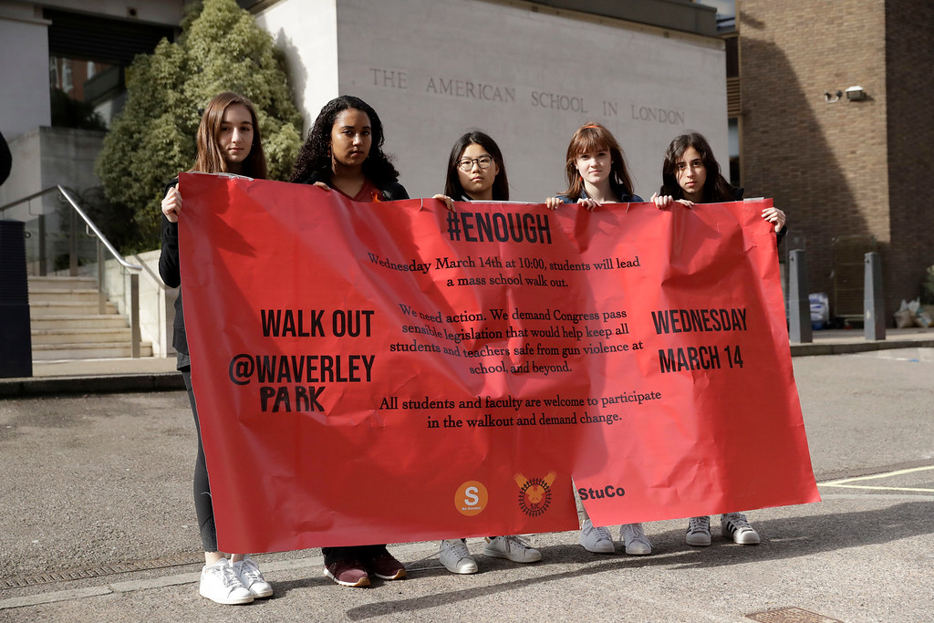 . Students, aged 17 & 18, pose for photographs with a banner outside the front of the American School in London, after taking part in a 10am local-time, 17-minute walkout in the school playground, which was attended by approximately 300 students aged 14-18, Wednesday, March 14, 2018. From Maine to Hawaii, students planned to walk out of school Wednesday to protest gun violence in the biggest demonstration yet of the student activism that has emerged in response to last month\'s massacre of 17 people at Florida\'s Marjory Stoneman Douglas High School. (AP Photo/Matt Dunham)