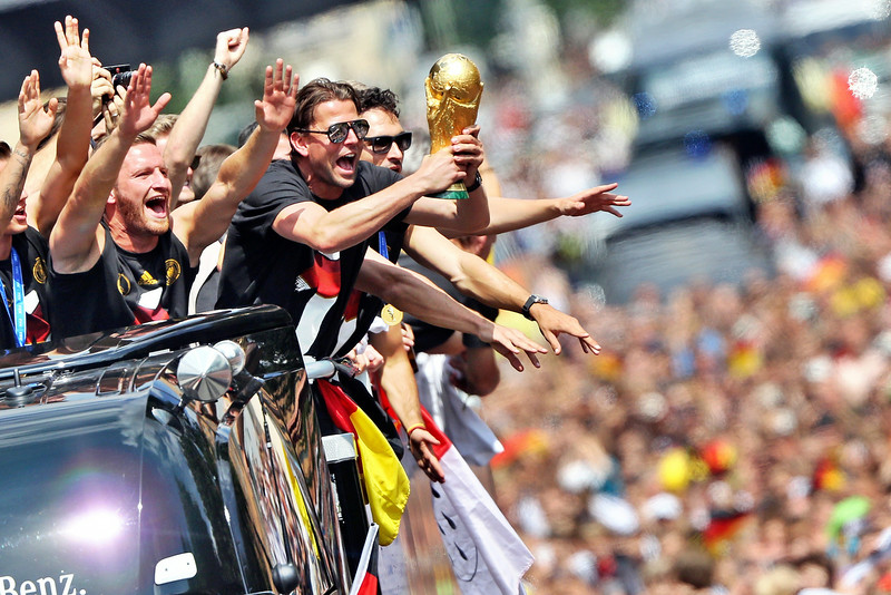 . German national football team players cheer as they ride in an open-deck bus to Berlin\'s landmark Brandenburg Gate to celebrate their FIFA World Cup title. Germany won their fourth World Cup title, after 1-0 win over Argentina on July 13, 2014 in Rio de Janeiro in the FIFA World Cup Brazil final game.  (JAN WOITAS/AFP/Getty Images)