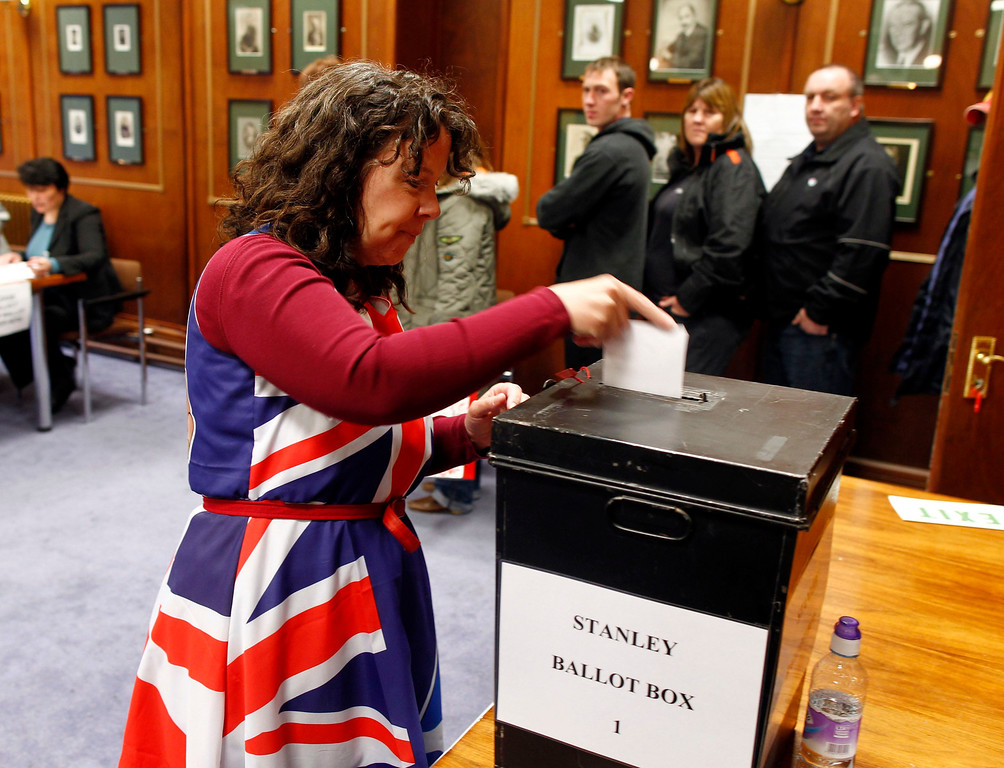 . Falkland Islander Joan Turner, wearing a dress with the Union Jack colours, casts her vote at the Town Hall polling station in Stanley, March 10, 2013. Residents of the Falkland Islands started voting on Sunday in a sovereignty referendum that seeks to counter Argentina\'s increasingly assertive claim over the British-ruled territory. REUTERS/Marcos Brindicci
