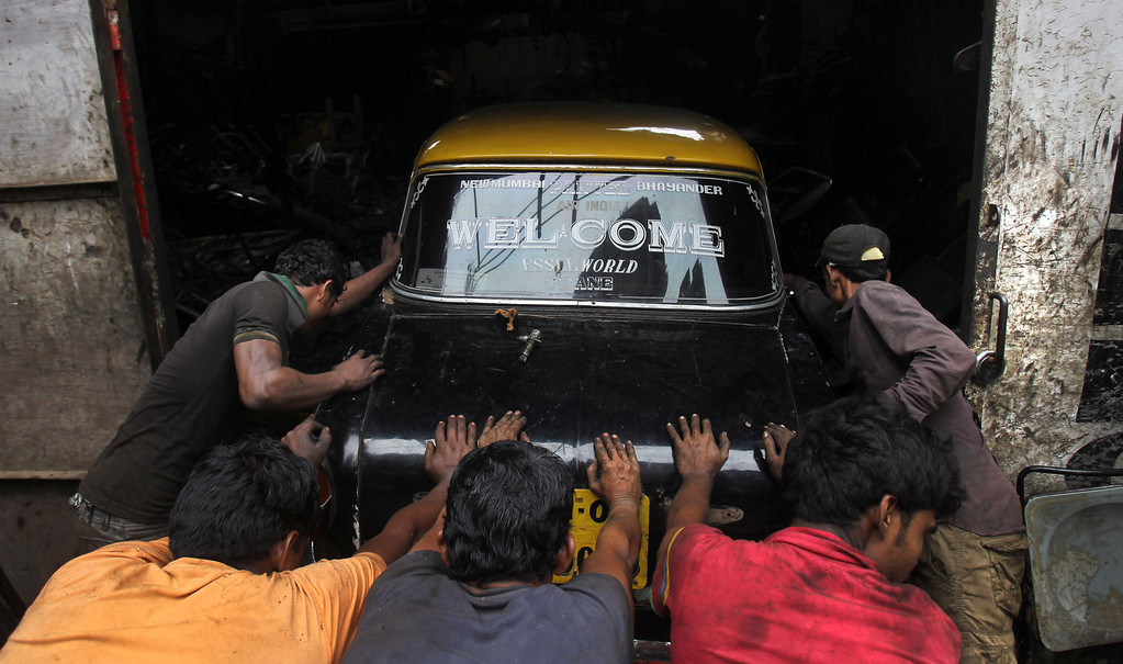 . In this Wednesday, July 31, 2013, Indian workers push a Mumbai Premier Padmini taxi into a scrapyard for dismantling, in Mumbai, India. More than 4500 Premier Padmini taxis are expected to be banned from the roads in Mumbai this year, starting in August,  in line with a government order that bans cabs that are more than 20 years old. (AP Photo/Rafiq Maqbool)