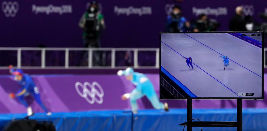 . A TV screen shows Pedro Causil of Colombia, left on TV and rear left, and Stanislav Palkin of Kazakhstan, right on TV and rear center, competing during the men\'s 500 meters speedskating race at the Gangneung Oval at the 2018 Winter Olympics in Gangneung, South Korea, Monday, Feb. 19, 2018. (AP Photo/Petr David Josek)