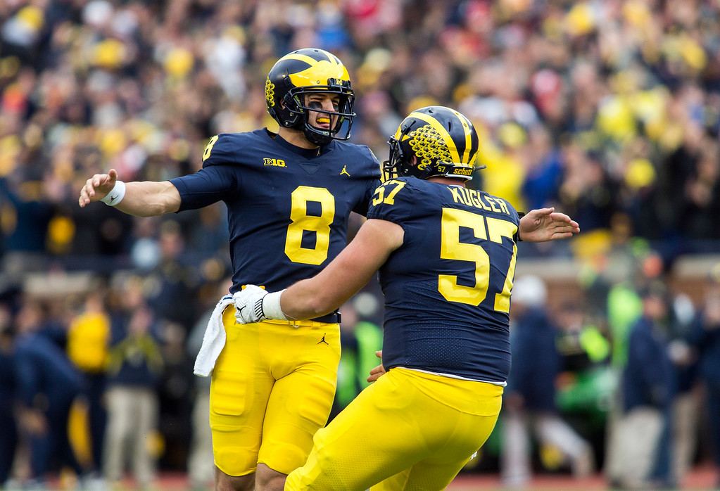 . Michigan quarterback John O\'Korn (8) celebrates a touchdown with offensive lineman Patrick Kugler (57) in the second quarter of an NCAA college football game against Ohio State in Ann Arbor, Mich., Saturday, Nov. 25, 2017. (AP Photo/Tony Ding)