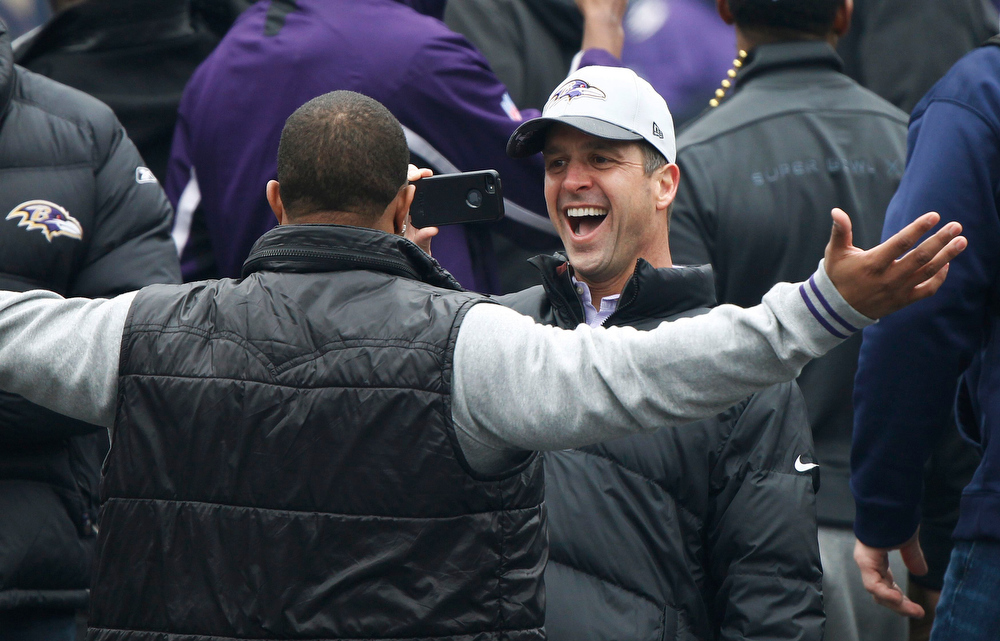 Description of . Super Bowl XLVII champion Baltimore Ravens head coach John Harbaugh (R) takes a photo of team running back Ray Rice (L) at a team and fan victory rally in Baltimore February 5, 2013. The Ravens defeated the San Francisco 49ers to win the NFL championship.     REUTERS/Gary Cameron
