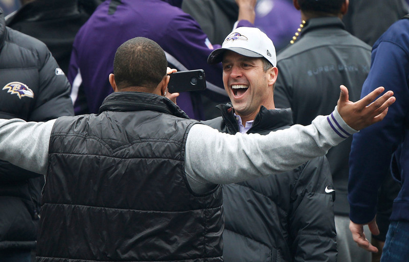 . Super Bowl XLVII champion Baltimore Ravens head coach John Harbaugh (R) takes a photo of team running back Ray Rice (L) at a team and fan victory rally in Baltimore February 5, 2013. The Ravens defeated the San Francisco 49ers to win the NFL championship.     REUTERS/Gary Cameron