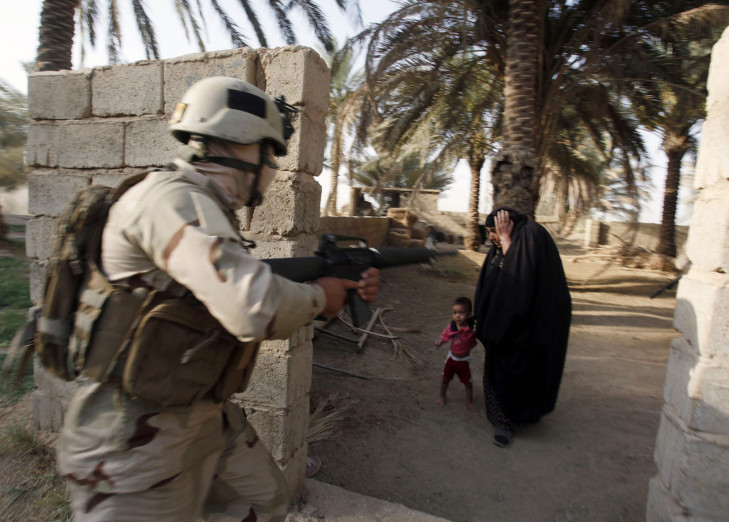 . In this photo taken on Friday, July 20, 2012, a woman and her child react as Iraqi soldiers raid her house in Arab Jabour, south of Baghdad, Iraq. Iraqi security forces raided some villages in Arab Jabour and detained 54 men suspected members of al-Qaida. (AP Photo/Alaa al-Marjani)