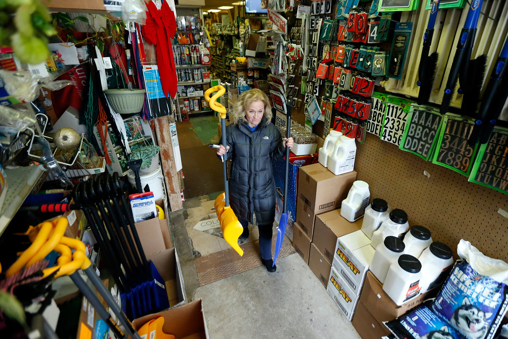 . Donna Przychodzki, of Secaucus, N.J., leaves Meadowlands Hardware with two snow shovels purchased in preparation for the weekend\'s storm, Friday, Jan. 22, 2016, in Rutherford, N.J. Towns across the state are hunkering down in preparation for a major snowstorm expected to begin later in the day. (AP Photo/Julio Cortez)