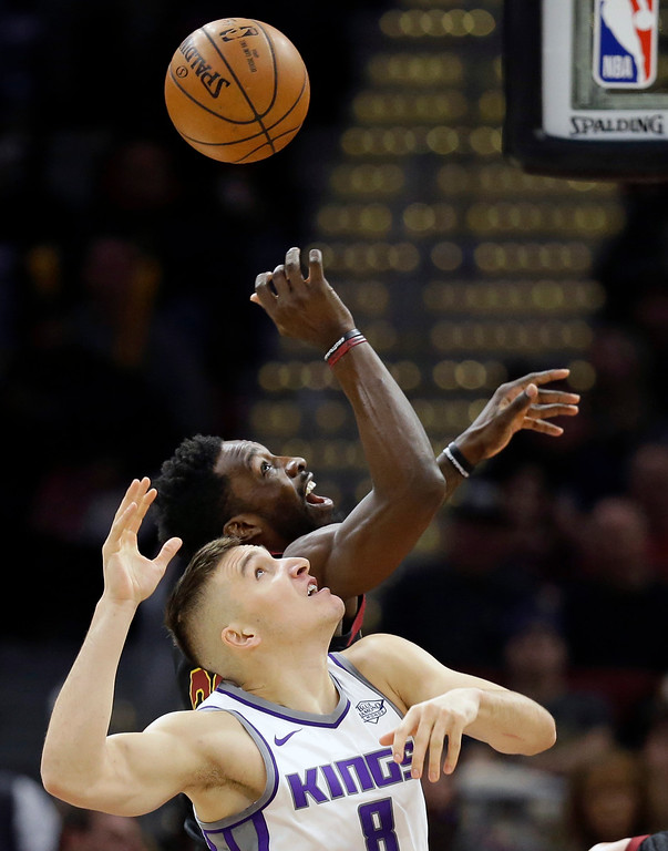 . Sacramento Kings\' Bogdan Bogdanovic (8), from Serbia, and Cleveland Cavaliers\' Jeff Green (32) battle for a rebound in the first half of an NBA basketball game, Wednesday, Dec. 6, 2017, in Cleveland. (AP Photo/Tony Dejak)