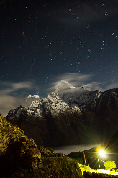 Thamserku and Kangtega are seen under a sky full of stars from the Sherpa village of Khumjung, Nepal