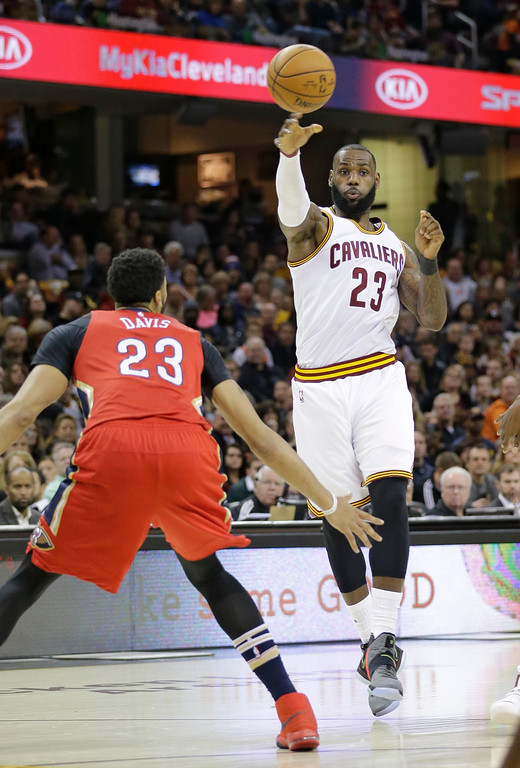 . Cleveland Cavaliers\' LeBron James, right, passes over New Orleans Pelicans\' Anthony Davis in the first half of an NBA basketball game, Monday, Jan. 2, 2017, in Cleveland. (AP Photo/Tony Dejak)