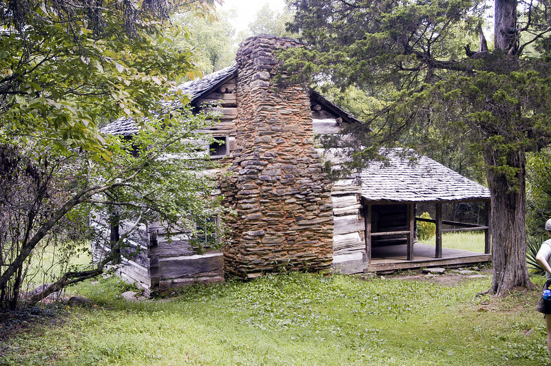 Log cabin with big stone fireplace surrounded by trees.