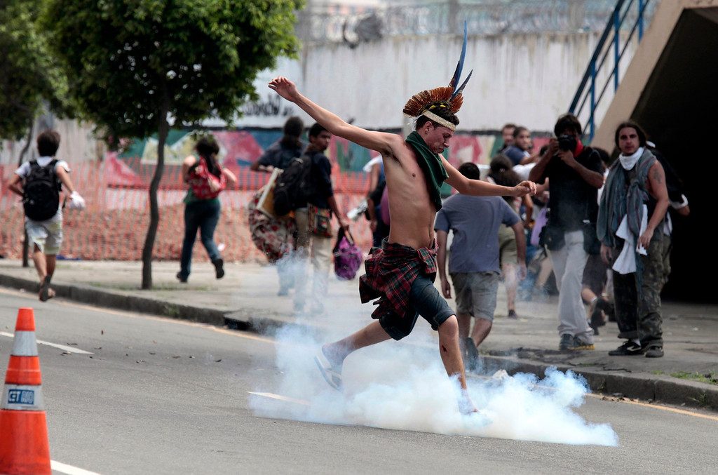 . A supporter of the native Indian community kicks a tear gas canister near the Brazilian Indian Museum in Rio de Janeiro March 22, 2013. Brazilian military police took position early morning outside the abandoned Indian museum, where a native Indian community of around 30 individuals have been living since 2006. The Indians were summoned to leave the museum in 72 hours by court officials since last week, local media reported. The group is fighting against the destruction of the museum, which is next to the Maracana Stadium. REUTERS/Sergio Moraes