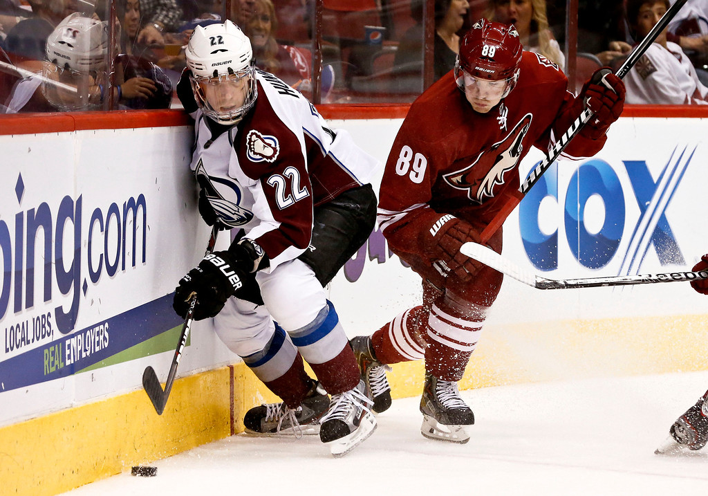 . Colorado Avalanche\'s Matt Hunwick (22) tries to keep the puck away from Phoenix Coyotes\' Mikkel Boedker (89), of Denmark, during the second period in an NHL hockey game, on Friday, April 26, 2013, in Glendale, Ariz.  The Avalanche defeated the Coyotes 5-4 in a shootout. (AP Photo/Ross D. Franklin)