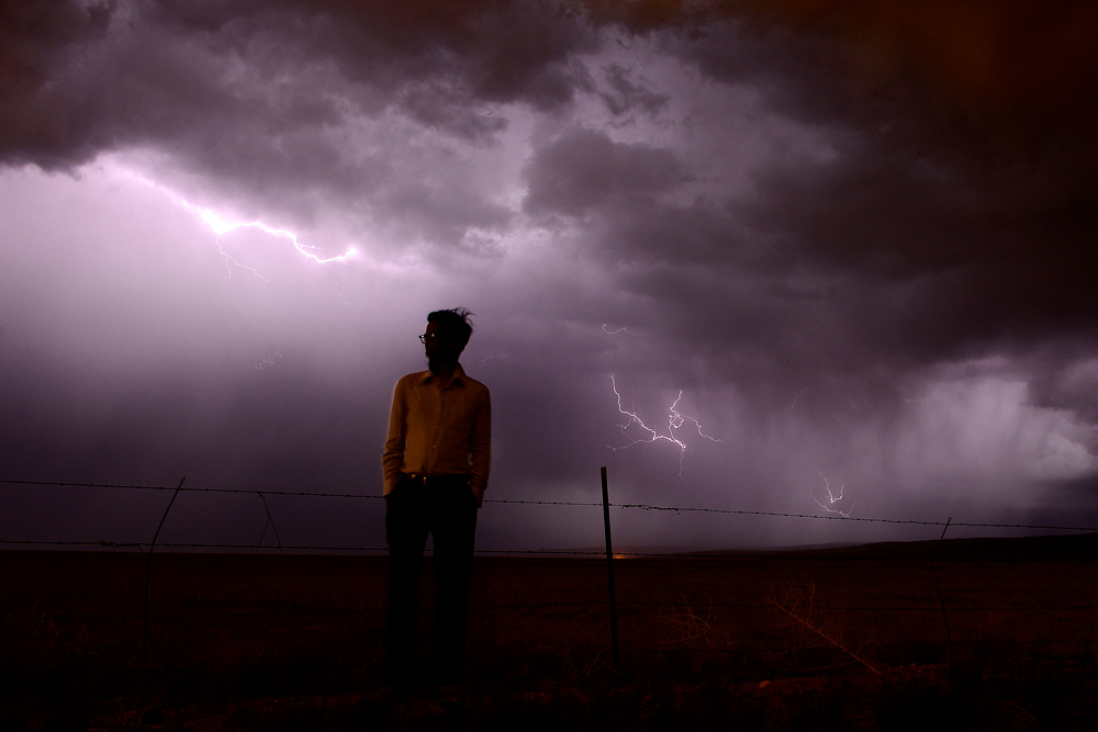 Description of . LARAMIE, WY - JUNE 09: Valentino Romero watches as a thunderstorm lights up the sky of northern Albany County, Wyoming about 10 miles north of Laramie. Romero, 29, whose mother was struck and killed by a vehicle on Federal Boulevard in Denver, took in the thunderstorm following his mother's services in their hometown. On this day, Valentino said goodbye to his mother and in the eulogy, he said,