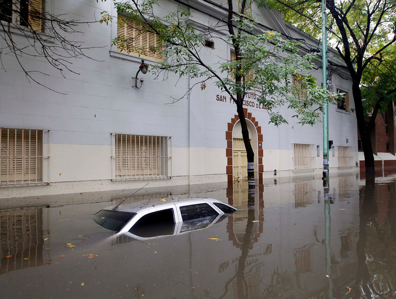 . A submerged car is seen in a flooded street after a rainstorm in Buenos Aires April 2, 2013. Thunderstorms damaged property and vehicles, cut power and caused delays on flights in Buenos Aires and its suburbs. The City\'s SAME emergency service announced that the death toll has risen to five.    REUTERS/Enrique Marcarian