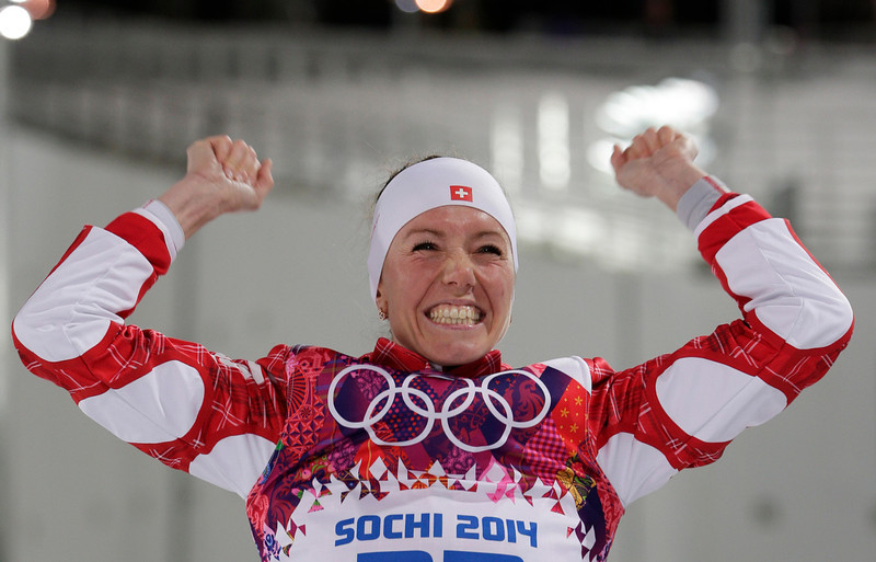 . Switzerland\'s Selina Gasparin celebrates winning the silver medal during flower ceremony for the women\'s 15K individual biathlon race at the 2014 Winter Olympics, Friday, Feb. 14, 2014, in Krasnaya Polyana, Russia. (AP Photo/Matthias Schrader)