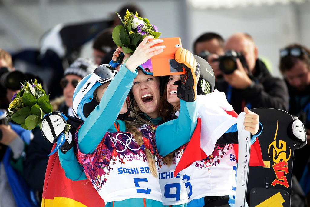 . Bronze medalist Amelie Kober, from left, of Germany silver medalist Anke Karstens, also of Germany,and gold medalist Julia Dujmovits, of Austria, take pictures after their flower ceremony for the women\'s snowboard parallel slalom at the Rosa Khutor Extreme Park, at the 2014 Winter Olympics, Saturday, Feb. 22, 2014, in Krasnaya Polyana, Russia. (AP Photo/Jae C. Hong)