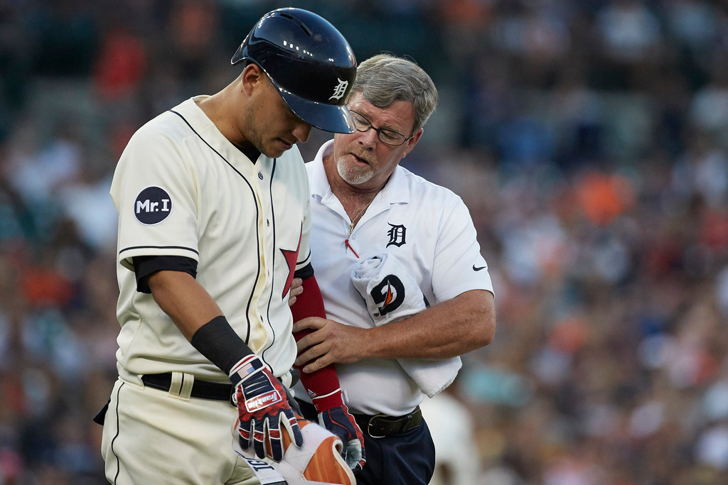 . Detroit Tiger Jose Iglesias is checked by trainer Kevin Rand after he is hit by a pitch during the fourth inning against the Cleveland Indians in the second baseball game of a doubleheader in Detroit, Saturday, July 1, 2017. (AP Photo/Rick Osentoski)