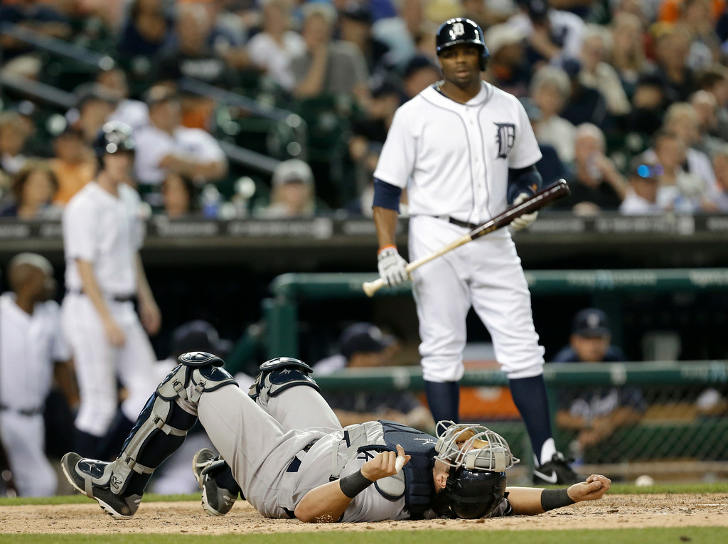 . New York Yankees catcher Francisco Cervelli lies at home plate after being hit by a pitch as Detroit Tigers\' Rajai Davis looks on in the fifth inning of a baseball game in Detroit, Wednesday, Aug. 27, 2014. (AP Photo/Paul Sancya)