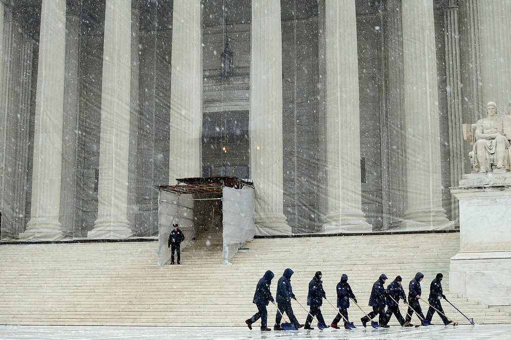 . Workers use shovels and brooms to remove a heavy mixture of snow and ice from the west front of the U.S. Supreme Court March 6, 2013 in Washington, DC. A late winter storm is expected to cover the Mid-Atlantic region after dropping almost a foot of snow across the the West and Midwest.  (Photo by Chip Somodevilla/Getty Images)
