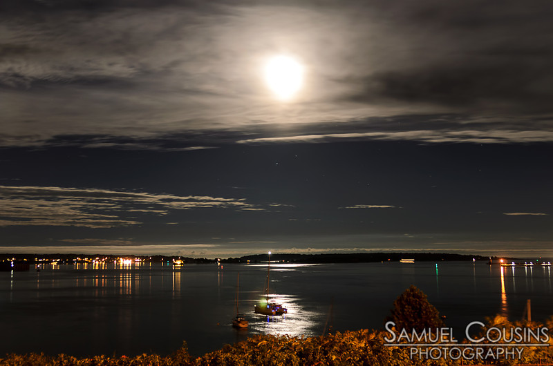 A long exposure of the full moon in the sky over Portland Harbor.  Long exposures at night can look like day, but you can also see starts in the sky as well.
