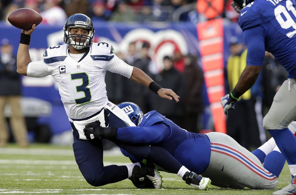 . Seattle Seahawks quarterback Russell Wilson (3) is sacked by New York Giants defensive tackle Linval Joseph during the first half of an NFL football game, Sunday, Dec. 15, 2013, in East Rutherford, N.J. (AP Photo/Kathy Willens)