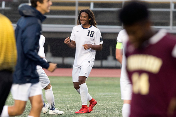 10/29/19 Wesley Bunnell | StaffrrNew Britain soccer was defeated 2-0 by Newington during a drizzle at Veterans Stadium on Tuesday afternoon. Mannasah Dalomba (18) smiles as teammates run onto he field after the victory.