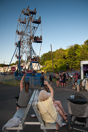 07/12/18 Wesley Bunnell | Staff People waive to their family and friends as they ride the ferris wheel on the first night of the Holy Cross Church's Sixty-'Fourth Bazaar and Carnival on Thursday night.