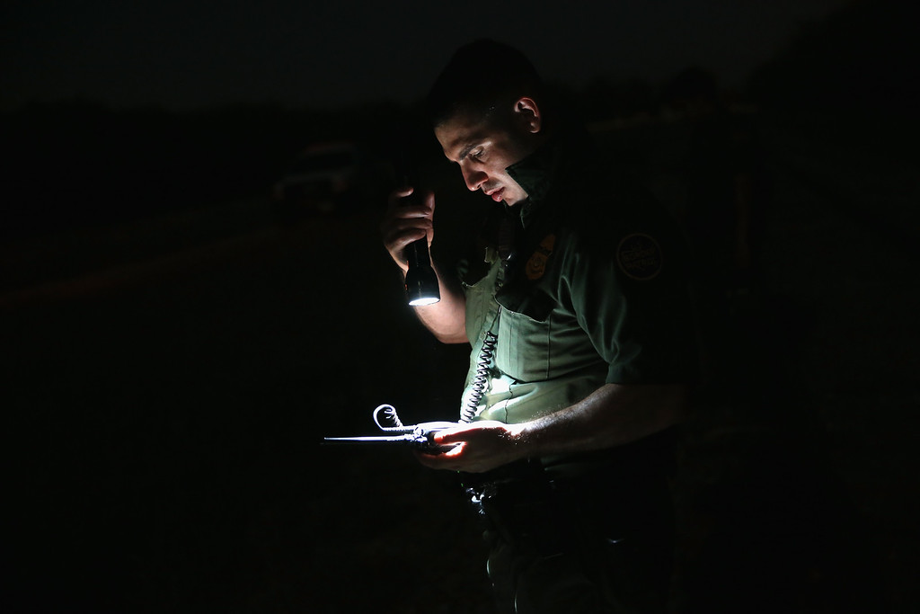 . A U.S. Border Patrol agent prepares a report after he and colleagues detained an undocumented immigrant near the Rio Grande River at the U.S.-Mexico border on September 8, 2014 near McAllen, Texas.  (Photo by John Moore/Getty Images)