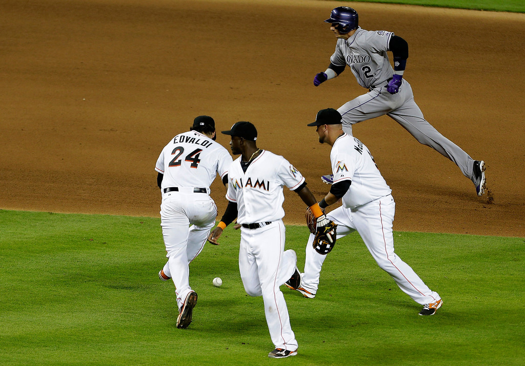 . Colorado Rockies\' Troy Tulowitzki (2) runs safely to third as Miami Marlins starting pitcher Nate Eovaldi (24), shortstop Adeiny Hechavarria, center, and third baseman Casey McGehee, right, can\'t come up with the ball in the fourth inning of a baseball game, Tuesday, April 1, 2014, in Miami. (AP Photo/Lynne Sladky)