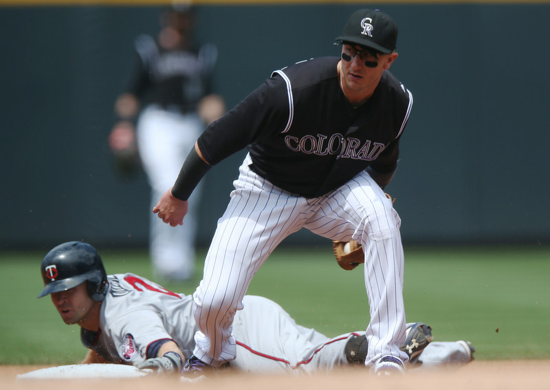 . Colorado Rockies shortstop Troy Tulowitzki, front, fields throw as Minnesota Twins\' Brian Dozier slides safely into second base with a double in the first inning of an interleague baseball game in Denver on Saturday, July 12, 2014. (AP Photo/David Zalubowski)
