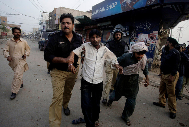 . Pakistani police officers detain two protestors, during clashes in Lahore, Pakistan, Sunday, March 10, 2013. Hundreds of Christians protesting the burning of their homes by a Muslim mob over alleged blasphemous remarks made against the Islam\'s Prophet Muhammad clashed with police on Sunday in eastern and southern Pakistan. (AP Photo/K.M. Chaudary)