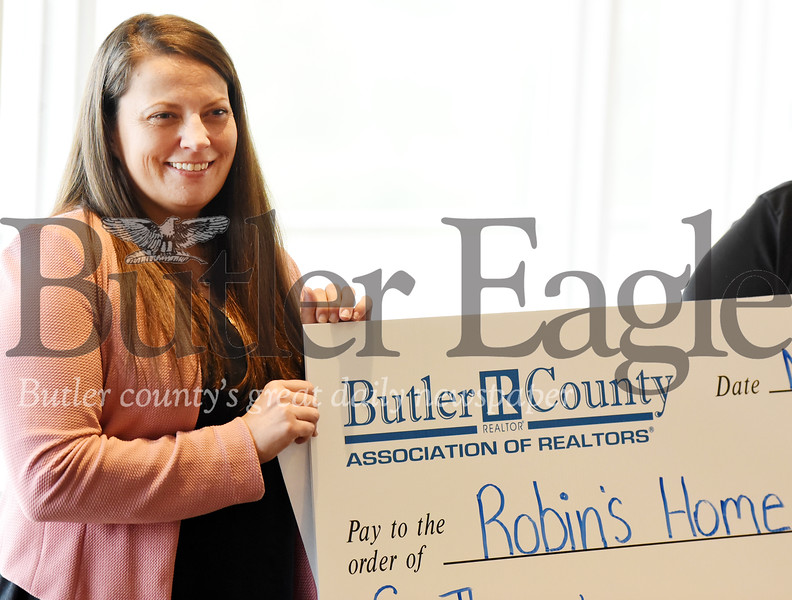 Harold Aughton/Butler Eagle: Mary Chitwood, executive director of Robin's Home, accepts a check from the Butler Association of Realtors Thurs., Nov. 21, 2019 at the Butler Country Club.