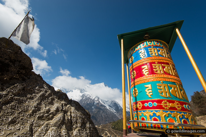 Large buddhist prayer wheel, flag and carved mani stone at the top of Namche