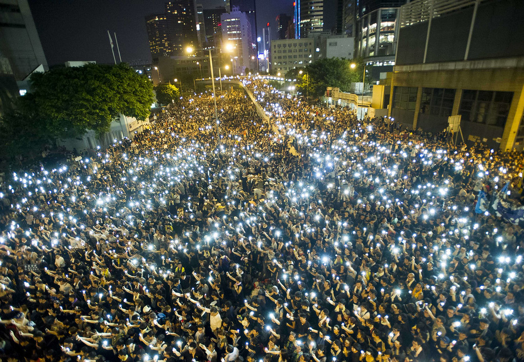 . Protestors and student demonstrators hold up their cellphones in a display of solidarity during a protest outside the headquarters of Legislative Council in Hong Kong on September 29, 2014. Hong Kong has been plunged into the worst political crisis since its 1997 handover as pro-democracy activists take over the streets following China\'s refusal to grant citizens full universal suffrage. AFP PHOTO / XAUME OLLEROS/AFP/Getty Images