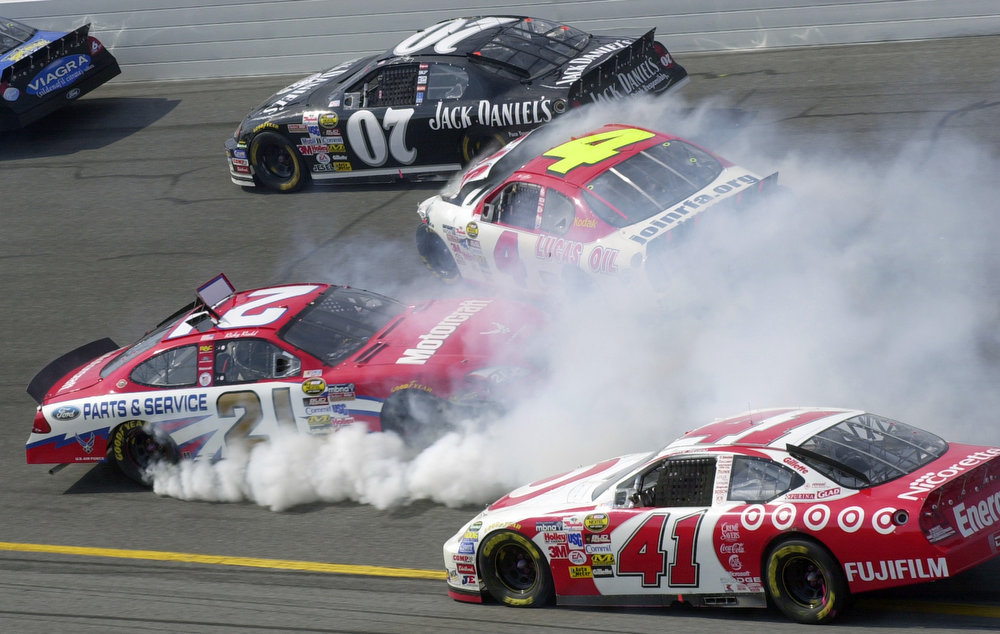Description of . NASCAR driver Ricky Rudd (21) and Mike Wallace (4) collide during a six car incident in Turn 4 during the Daytona 500 at the Daytona International Speedway in Daytona Beach, Fla., on Sunday, Feb. 20, 2005. At Top is Dave Blaney (07). At bottom is Casey Mears (41).  (AP Photo/Paul Kizzle)
