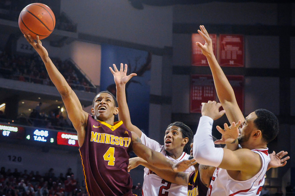 . Minnesota Golden Gophers guard Deandre Mathieu (4) takes a shot in front of Nebraska Cornhuskers forward David Rivers (2) and Nebraska Cornhuskers forward Walter Pitchford (35). (AP Photo/Dave Weaver)