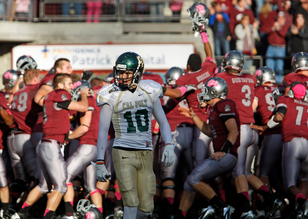 . Cal Poly wide receiver Carson McMurtrey(10) walks away as Montana celebrates a 21-14 victory in overtime in an NCAA college football game in Missoula, Mont., Saturday, October 19, 2013. (AP Photo/Michael Albans)