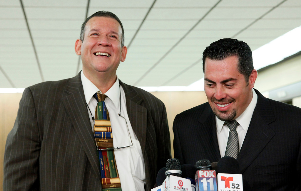 . Former Councilman Luis Artiga, left, celebrates his acquittal, standing with his attorney George Mgdesyan during a news conference after the Bell trial verdicts were read Wednesday March 20, 2013 in Los Angeles. Five former elected officials of the tiny California city of Bell were convicted Wednesday of multiple counts of misappropriation of public funds, and a sixth defendant, Artiga, was cleared entirely. (AP Photo/Nick Ut)