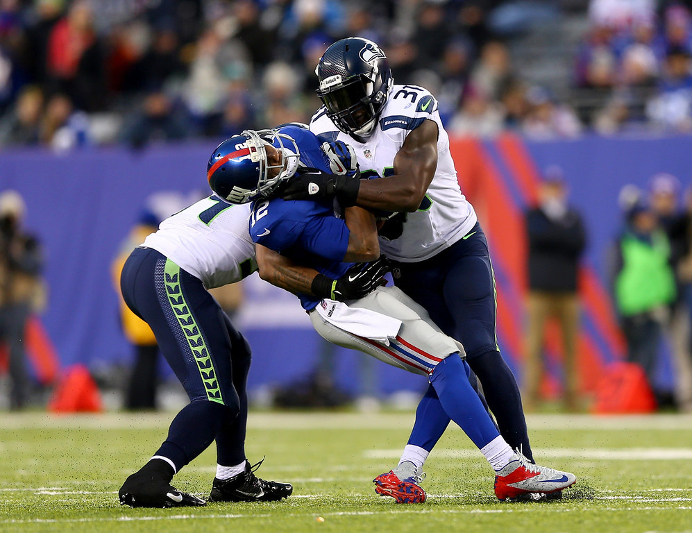 . Jerrel Jernigan #12 of the New York Giants is hit by  Kam Chancellor #31 of the Seattle Seahawks at MetLife Stadium on December 15, 2013 in East Rutherford, New Jersey.The Seattle Seahawks defeated the New York Giants 23-0.  (Photo by Elsa/Getty Images)