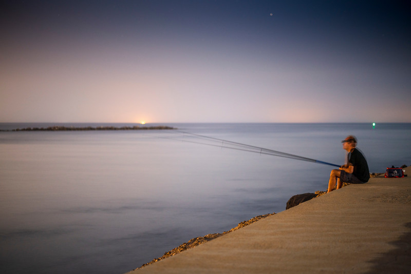 Angler fishing at night, Ayamonte, Spain
